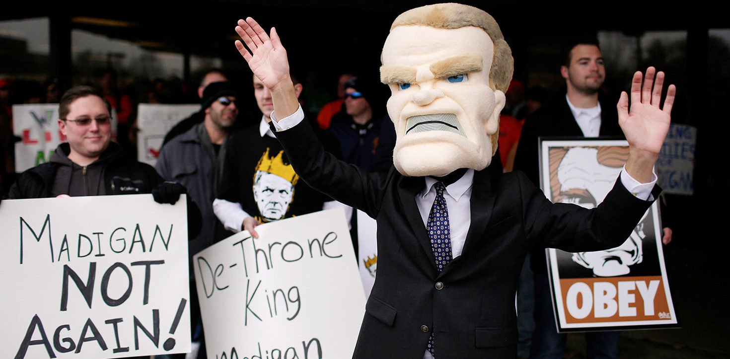 Demonstrators protest the possible re-election of Illinois of State Representative Michael Madigan as Speaker of the House as a supporter dressed as Madigan, center, dances with his hands up at the University of Illinois campus in Springfield, Illinois, U.S., January 11, 2017. Madigan was re-elected to his 17th term by a vote of 66-51. (PHOTO: REUTERS/Joshua Lott)