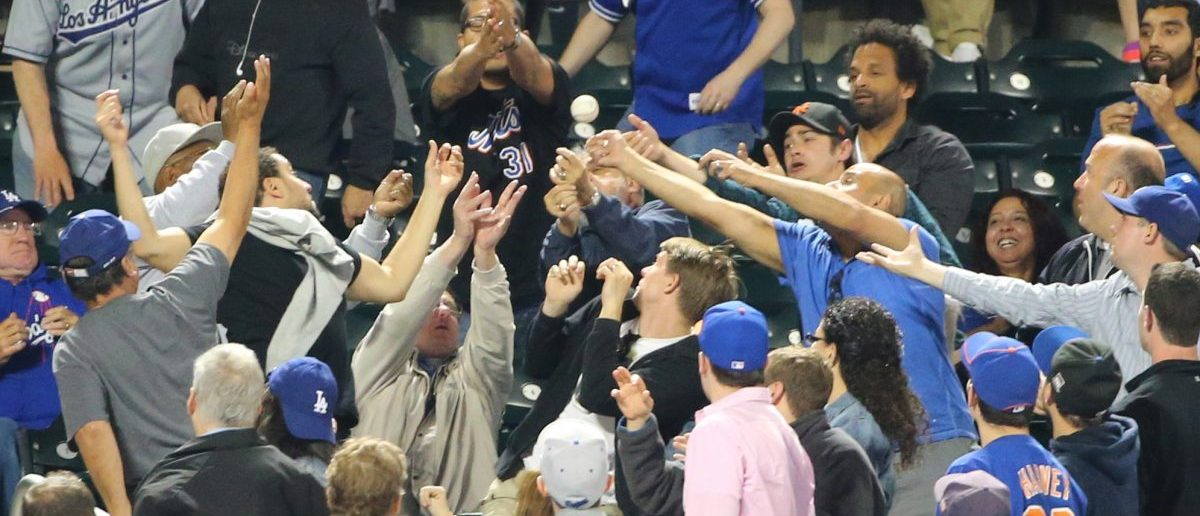 Fans reach for a foul ball during the ninth inning of the game between the New York Mets and the Los Angeles Dodgers at Citi Field. (Anthony Gruppuso-USA TODAY Sports)