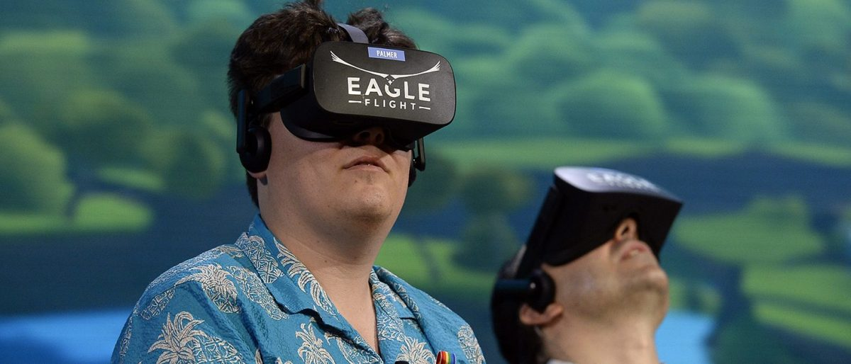 "Palmer Luckey, co-founder of Oculus VR Inc., left, plays the new video game ""Eagle Flight VR"" during an Ubisoft news conference before the start of the E3 Gaming Conference on June 13, 2016 in Los Angeles, California. (PHOTO: Kevork Djansezian/Getty Images)"
