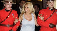 Pamela Anderson gets escorted by Canadian Mounties at an event (Photo: Reuters)