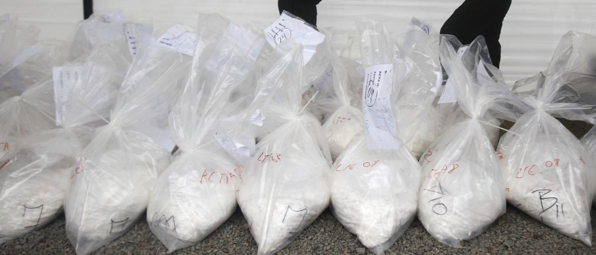 Anti-narcotics workers display bags containing cocaine in front of an incinerator in Lima September 22, 2011. More than six tons of drugs including cocaine paste, marijuana, cocaine and opium seized during police operations held between July and September were incinerated. REUTERS/Enrique Castro-Mendivil