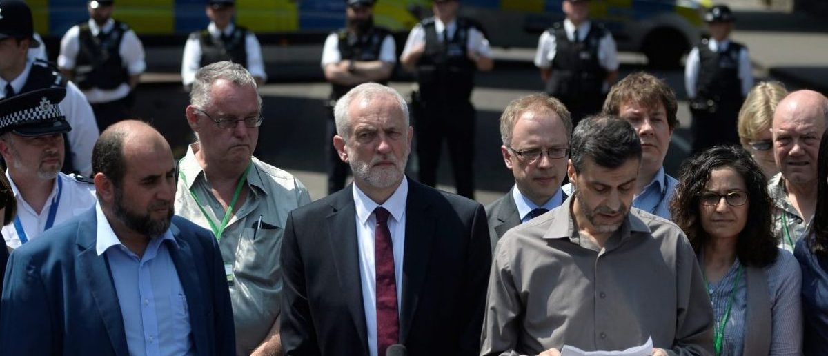 Jeremy Corbyn, the leader of Britain's opposition Labour Party and the local Member of Parliament, stands next to Mohammed Kozbar, general secretary of the Finsbury Park Mosque, as he reads a statement near to where a van was driven at muslims outside the mosque in North London, Britain, June 19, 2017. REUTERS/Hannah McKay - RTS17OQS
