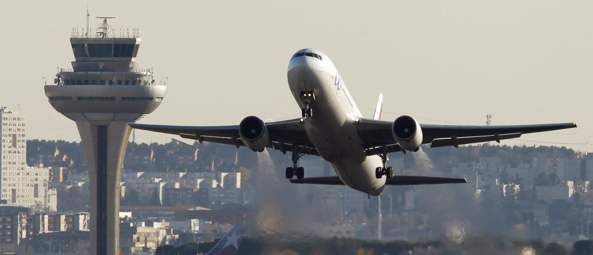 A passenger aircraft takes off past the air traffic control tower. (REUTERS/Sergio Perez)