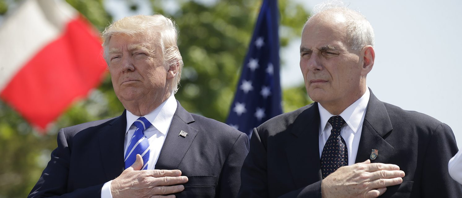 President Donald Trump (L) and U.S. Department of Homeland Security Secretary John Kelly hold their hands over their hearts for the U.S. National Anthem as they attend the Coast Guard Academy commencement ceremonies where Trump is addressing the graduating class in New London, Connecticut, U.S. May 17, 2017. (PHOTO: REUTERS/Kevin Lamarque)
