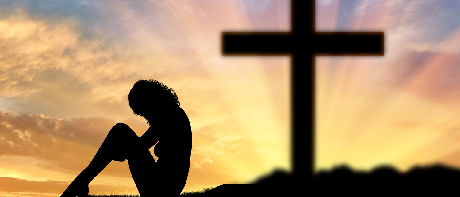 Atheism. Atheist woman sits with his back to the cross (Shutterstock/Prazis Images)