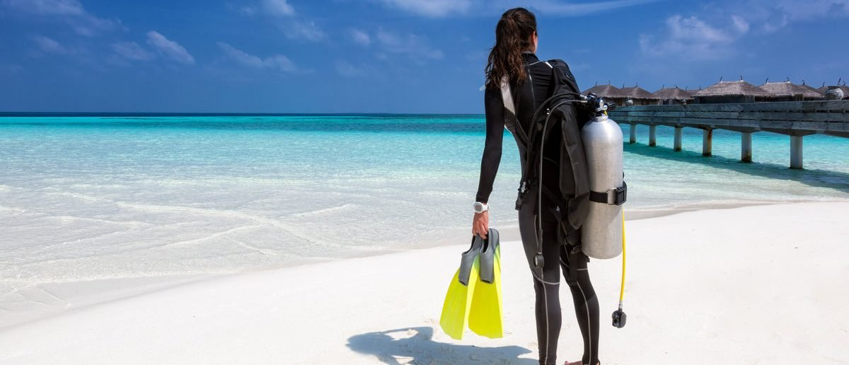 Female scuba diver with diving equipment on the beach at the Maldives (Shutterstock/Sven Hansche)