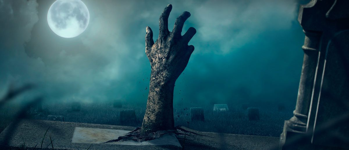 Zombie hands rising in dark Halloween night. (Shutterstock/chaiyapruek youprasert)