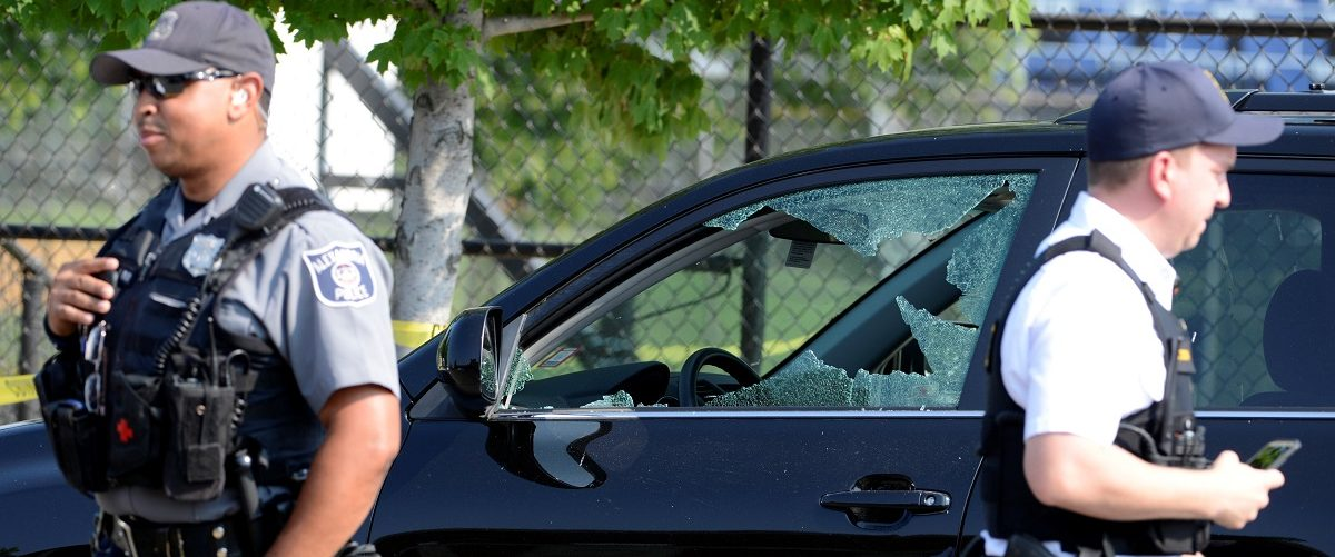 A vehicle window is shattered as police secure the scene where shots were fired during a Congressional baseball practice, wounding House Majority Whip Steve Scalise, in Alexandria