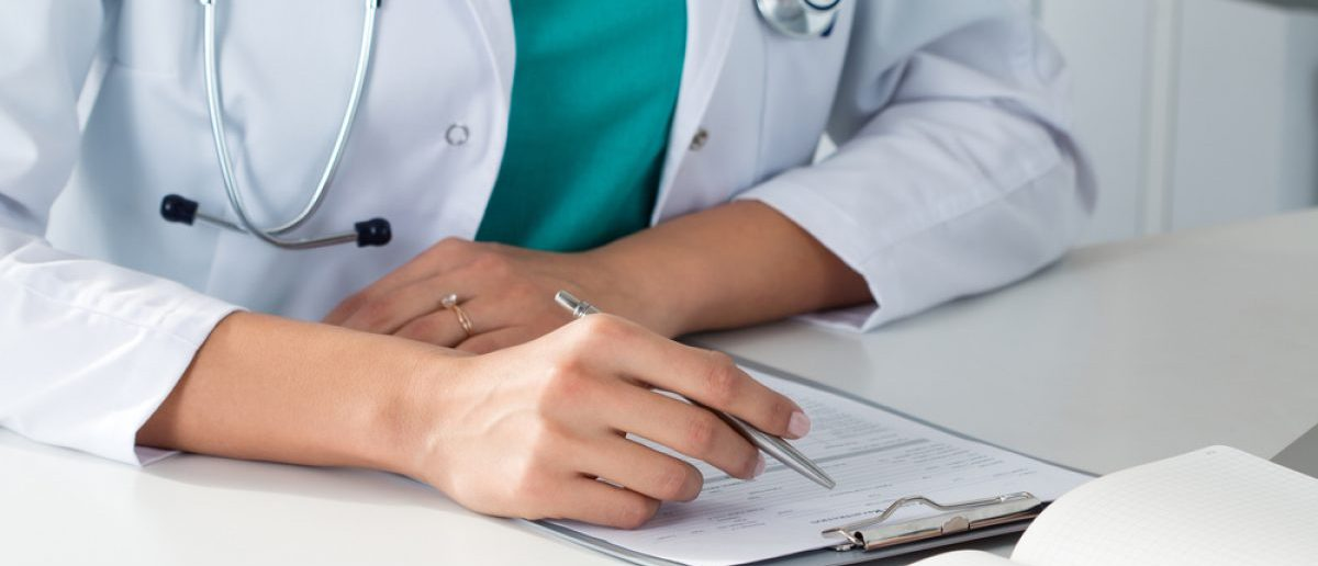 Doctor filling out medical records for a patient and fellow staff. [Shutterstock - Irenaphoto]