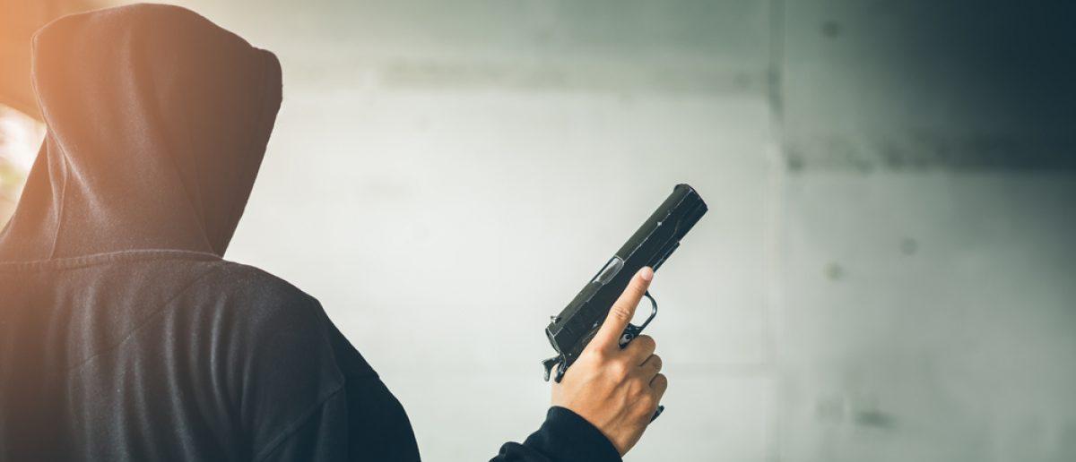 Gang member holds a gun. Source: Chayantorn Tongmorn/Shutterstock