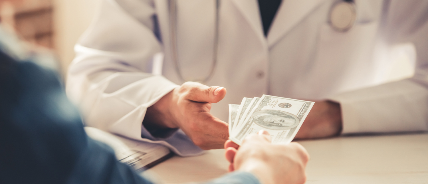 A doctor takes cash (Photo: Shutterstock/VGstockstudio)