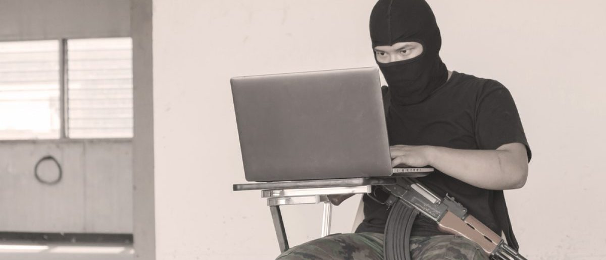 A terrorist using his computer to recruit and communicate with other operatives. [Shutterstock - Kom_Pornnarong]