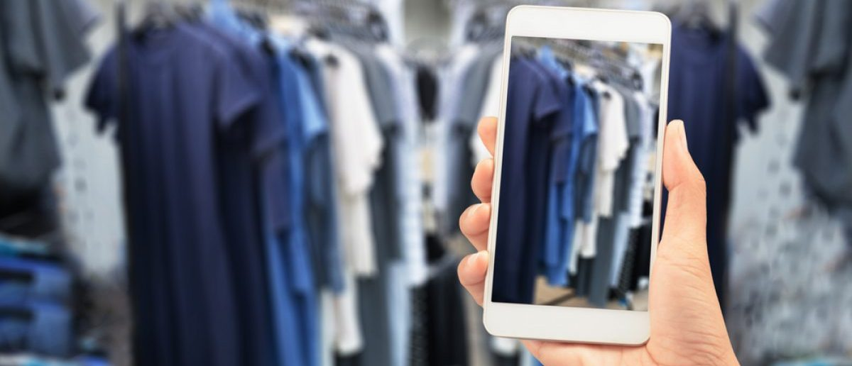 Woman using her smartphone to analyze clothes in the store. [Shutterstock - Sisacorn]