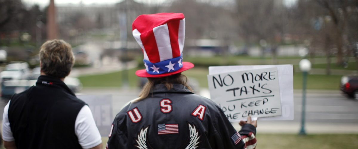 A protester holds up a sign while waiting for the Tea Party Express bus to arrive on the steps of the state capitol in Denver