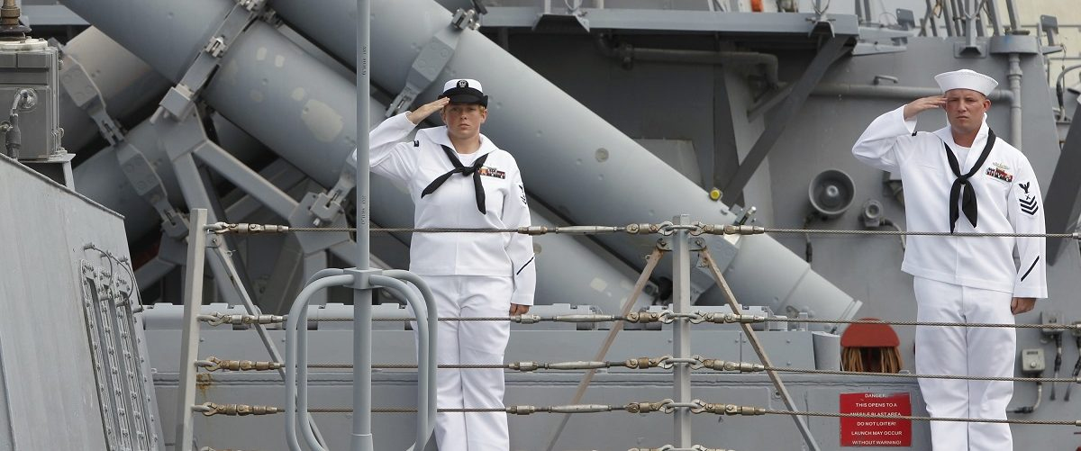 U.S. sailors salute in front of missile launchers onboard the USS Fitzgerald destroyer in Manila