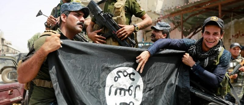 Iraqi Federal Police members hold an Islamic State flag, which they pulled down during fighting. REUTERS/Ahmed Saad