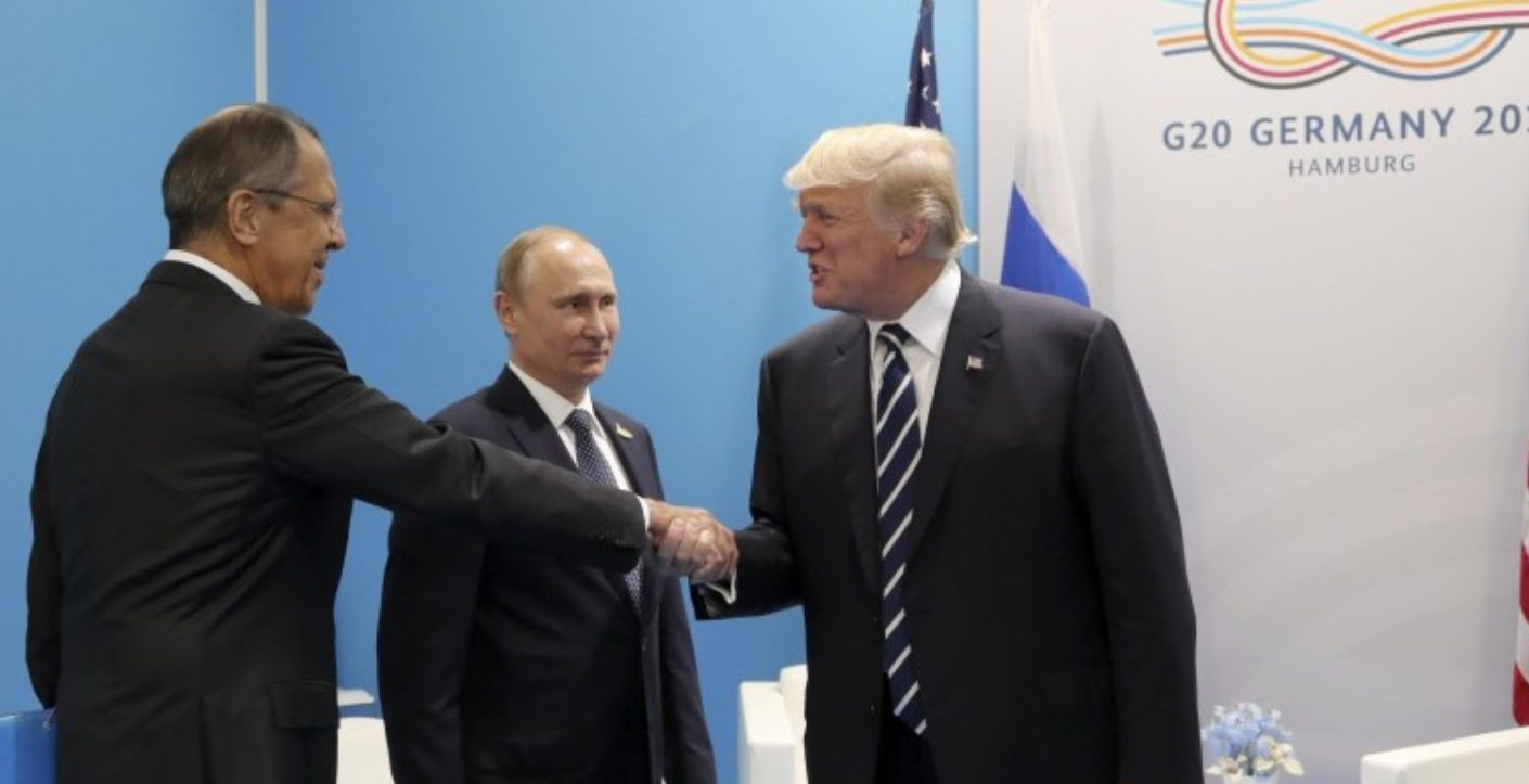 U.S. President Donald Trump (R) shakes hands with Russian Foreign Minister Sergei Lavrov as Russian President Vladimir Putin stands nearby during a meeting on the sidelines of the G20 summit in Hamburg, Germany July 7, 2017 Sputnik/Mikhail Klimentyev/Kremlin via REUTERS
