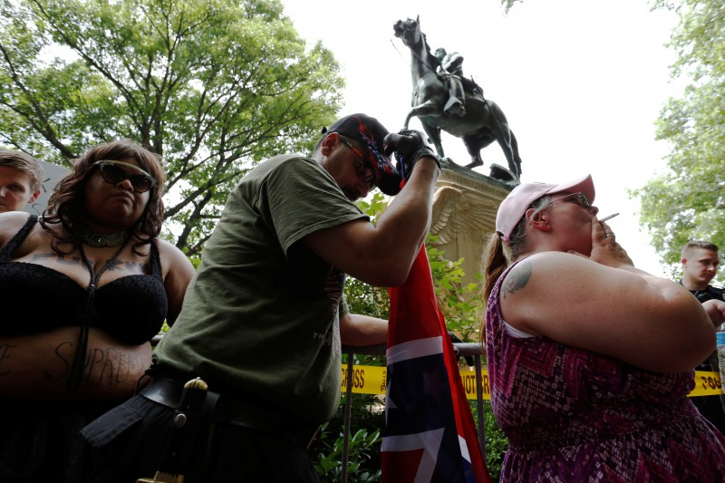 A woman (R) who supports Confederate symbols and monuments relaxes with a cigarette after she and her husband (C) exchanged words with a counter-protester as they wait for members of the Ku Klux Klan to rally in support of Confederate monuments, such as the statue of General Stonewall Jackson behind them, in Charlottesville, Virginia, U.S. July 8, 2017. REUTERS/Jonathan Ernst