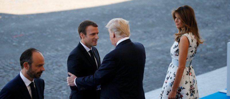 French President Emmanuel Macron shakes hands with U.S. President Donald Trump as U.S. First Lady Melania Trump looks on before the traditional Bastille Day military parade on the Champs-Elysees in Paris, France, July 14, 2017. At L, French Prime Minister Edouard Philippe.  REUTERS/Gonzalo Fuentes