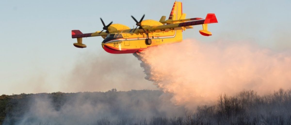 FILE PHOTO: A firefighting plane drops water to extinguish a forest fire near Zadar