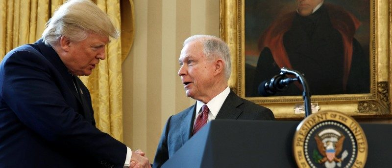FILE PHOTO - Under a portrait of former President Andrew Jackson, U.S. President Donald Trump (L) congratulates Jeff Sessions after he was sworn in as U.S. Attorney General during a ceremony in the Oval Office of the White House in Washington, U.S. on February 9, 2017. REUTERS/Kevin Lamarque/File Photo