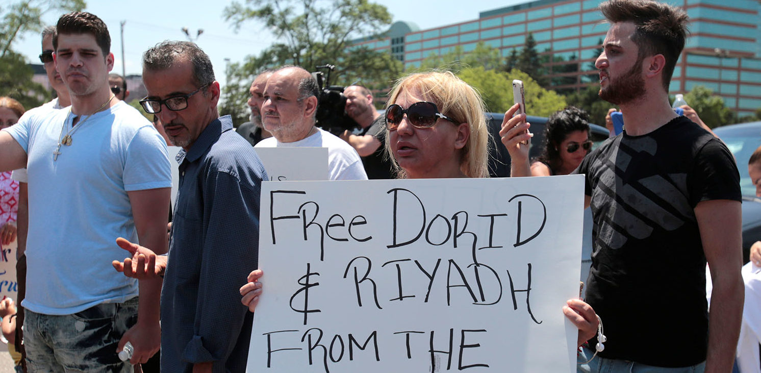 Chaldean-American Nadia Al-Raviah holds a sign protesting against the seizure of her husband and brother Sunday by Immigration and Customs Enforcement agents during a rally outside the Mother of God Chaldean church in Southfield, Michigan, U.S., June 12, 2017.   (PHOTO: REUTERS/Rebecca Cook)