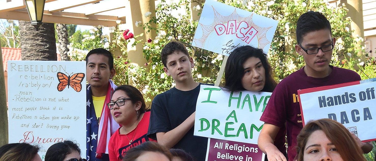 Children hold banners and placards while listening to speakers at a rally outside the 9th Circuit federal court in Pasadena, California on July 16, 2015, where Immigrant rights organizations, labor, and Deferred Action for Childhood Arrivals (DACA) recipients from Arizona and Los Angeles gathered. After a multiple-year legal battle, the state of Arizona's embattled efforts to deny driver's licenses to immigrants who have been granted DACA under a federal program will face what could be yet another blow to Arizona when the Court of Appeals for the Ninth Circuit hears oral arguments this Thursday in a lawsuit brought by civil rights groups challenging the discriminatory policy. (PHOTO: Getty Images/AFP/ FREDERIC J. BROWN)