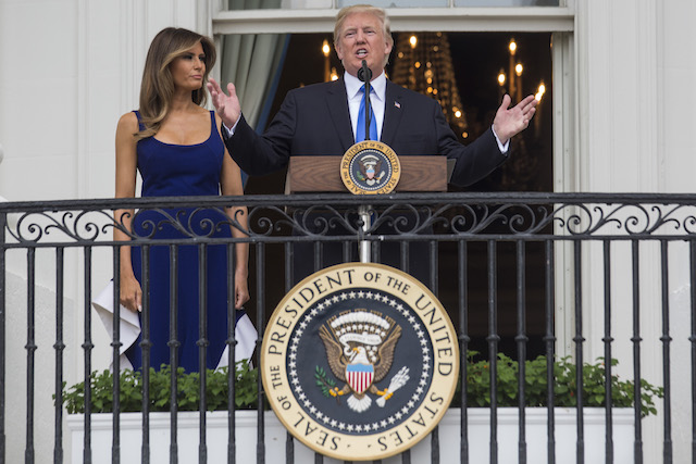 WASHINGTON, DC - JULY 4: U.S. President Donald Trump delivers remarks as first lady Melania Trump looks on from the Truman Balcony on July 4, 2017 in Washington, DC. The president was hosting a picnic for military families for the July 4 holiday. (Photo by Zach Gibson/Getty Images)