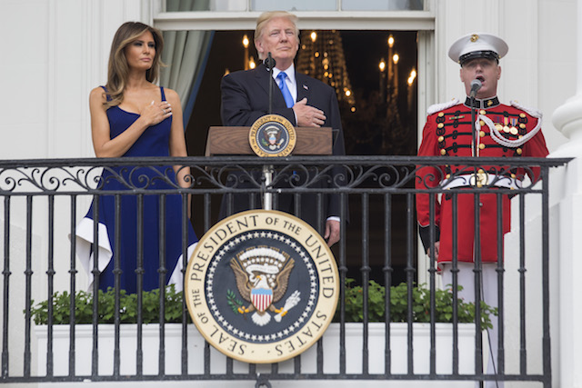 WASHINGTON, DC - JULY 4: U.S. President Donald Trump and first lady Melania Trump observe the playing of the national anthem from the Truman Balcony on July 4, 2017 in Washington, DC. The president was hosting a picnic for military families for the July 4 holiday. (Photo by Zach Gibson/Getty Images)