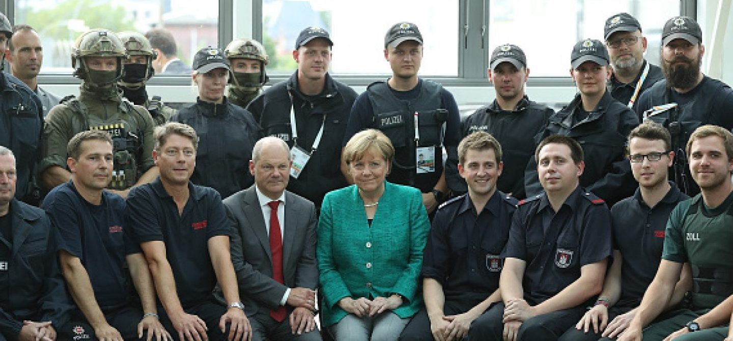 HAMBURG, GERMANY - JULY 08: German Chancellor Angela Merkel sits with members of German law enforcement and emergency services while thanking them at the conclusion of the G20 economic summit on July 8, 2017 in Hamburg, Germany. Severe rioting by anti-G20 activists that included looting, arson and physical attacks against police overshadowed the two-day summit. (Photo by Sean Gallup - Pool / Getty Images)