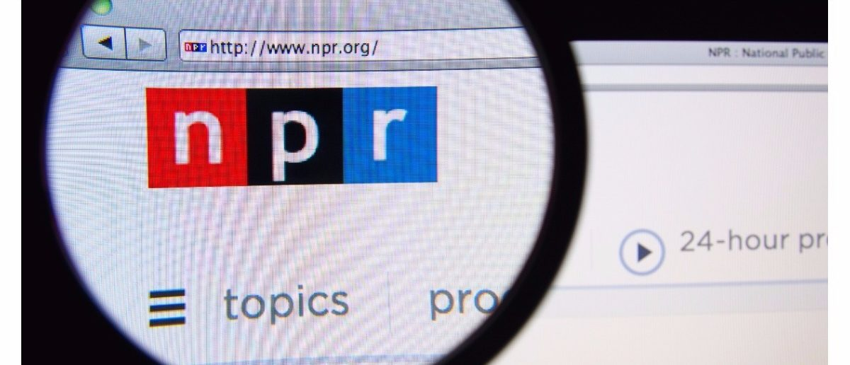 Photo of the National Public Radio homepage on a monitor screen through a magnifying glass (Shutterstock/Gil C)