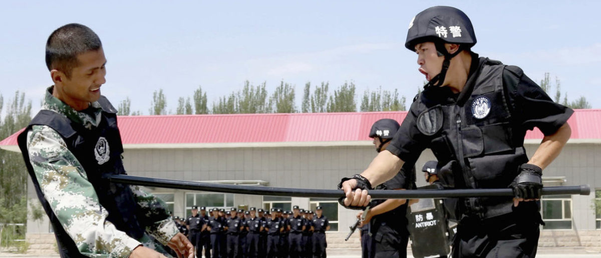 A policeman (R) from Special Weapons and Tactics (SWAT) team fights with a stick against a mock attacker during a graduation performance after training as members of an anti-terrorist patrol team, in Hami, Xinjiang Uighur Autonomous Region June 29, 2014. Picture taken June 29, 2014. REUTERS/China Daily (CHINA - Tags: MILITARY CRIME LAW) CHINA OUT. NO COMMERCIAL OR EDITORIAL SALES IN CHINA - RTR3WK9P