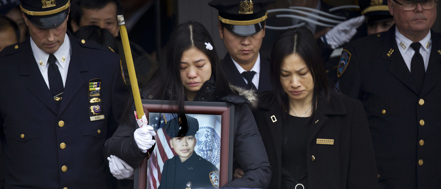 Widow Pei Xia Chen holds a photo of slain New York Police Department officer Wenjian Liu as his casket departs his funeral in the Brooklyn borough of New York January 4, 2015. REUTERS/Carlo Allegri