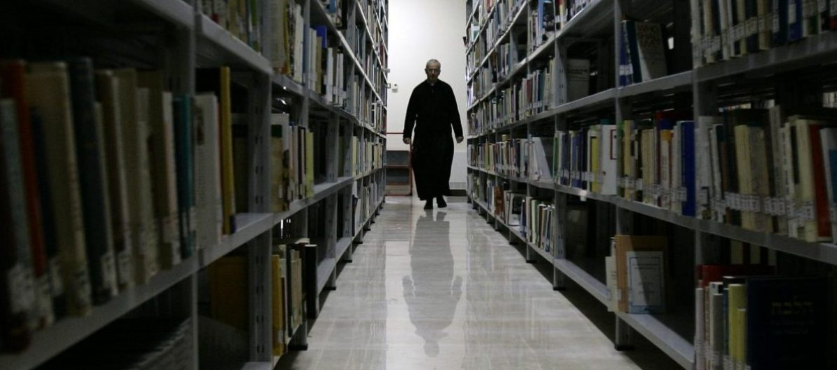 Professor at Rome's Regina Apolostolorum pontifical university walks though a libraby used in a new course on the occult. Francesco Bamonte, a professor at Rome's Regina Apolostolorum pontifical university, walks though a libraby used in a new course on the occult February 15, 2005. The university is holding a special course starting February 17, for Roman Catholic priests on Satanism and exorcism in response to what the Church says is a worrying interest in the occult, particularly among the young. REUTERS/Alessandro Bianchi - RTRNDI7