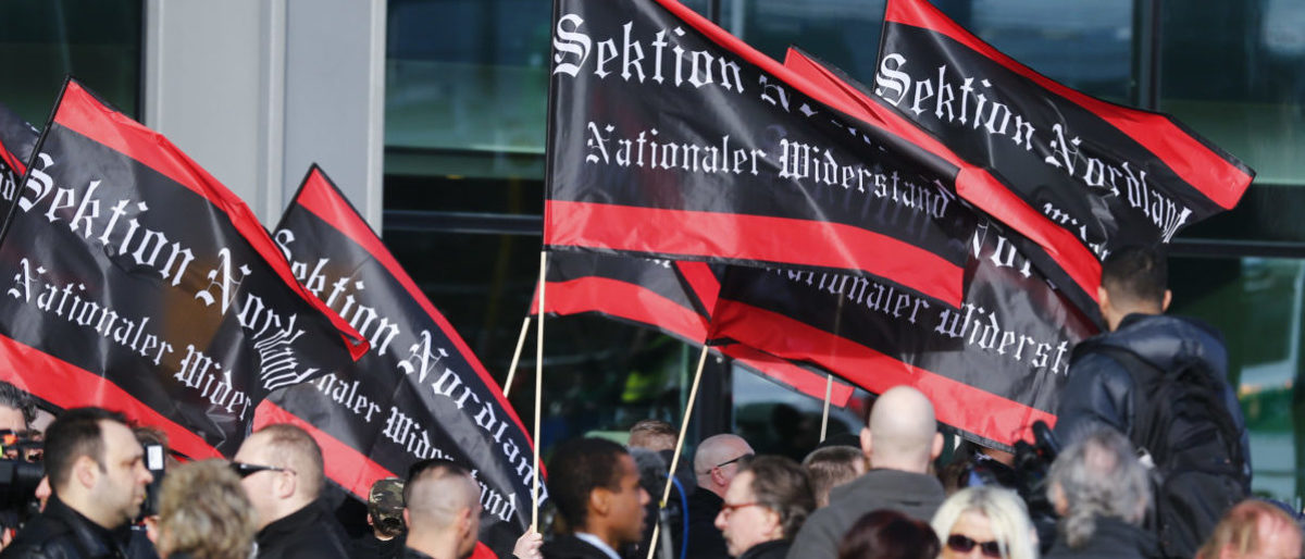 "Ultra right-wing protesters carry flags that read ""Section Northland - National Resistance""  during a rally against salafists in Berlin, Germany, March 4, 2017.     REUTERS/Hannibal Hanschke  - RTS11FH3"