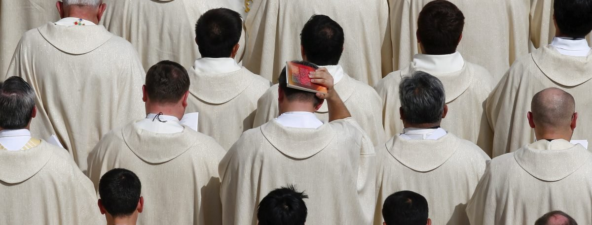 A priest covers his head with a book as Pope Francis celebrates a Jubilee mass in Saint Peter's Square at the Vatican, April 3, 2016. REUTERS/Tony Gentile - RTSDC69