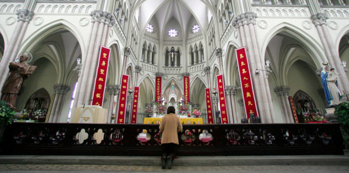 A Chinese Catholic prays on Easter Sunday at the state-sanctioned Saint Ignatius Cathedral in Shanghai March 27, 2005. To match Special Report CHINA-VATICAN/ REUTERS/Claro Cortes IV/File Photo - RTSHWCB