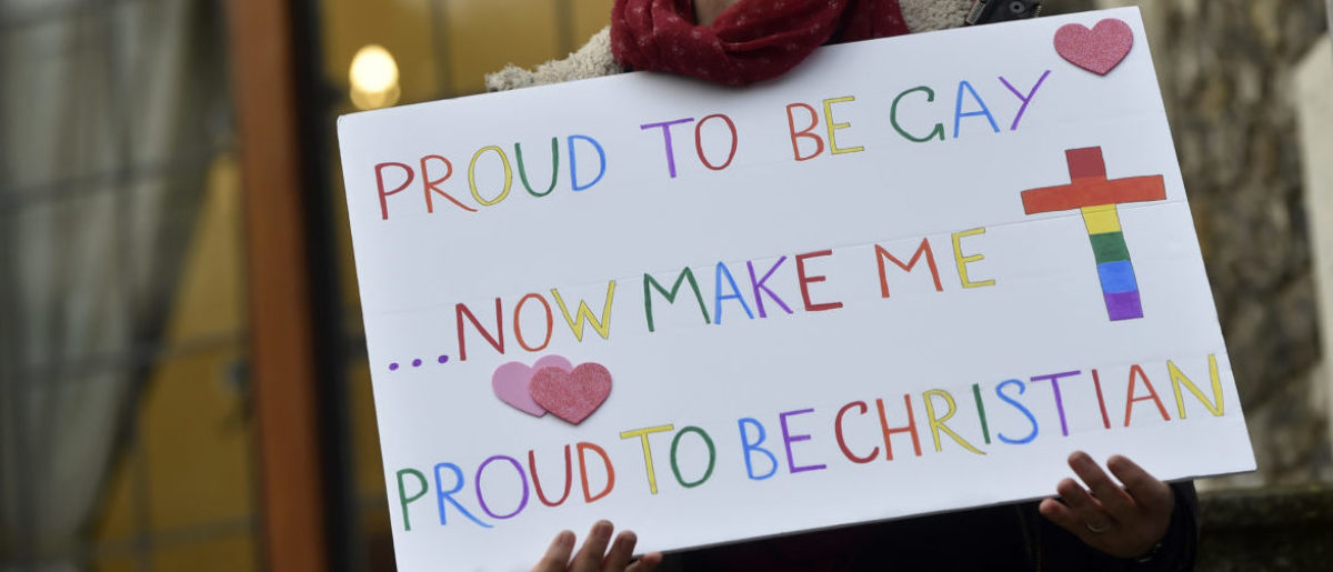 A woman holds a placard during a vigil against Anglican Homophobia, outside the General Synod of the Church of England in London, Britain, February 15, 2017. REUTERS/Hannah McKay - RTSYR0G