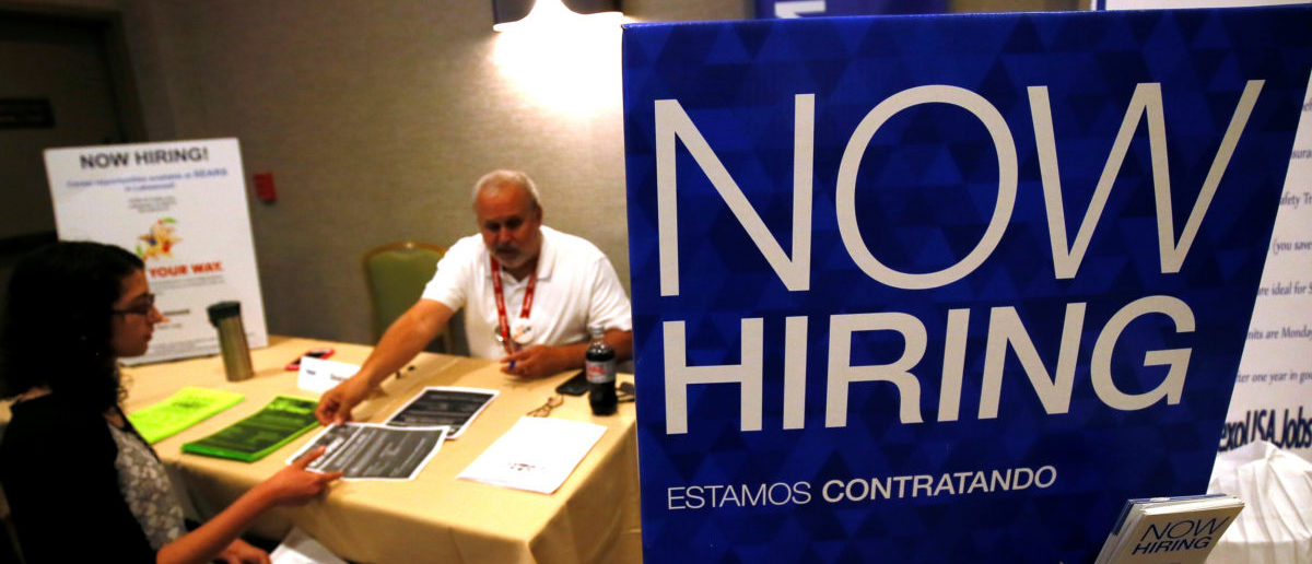A job applicant talks with a recruiter for Sears at a job fair in Golden