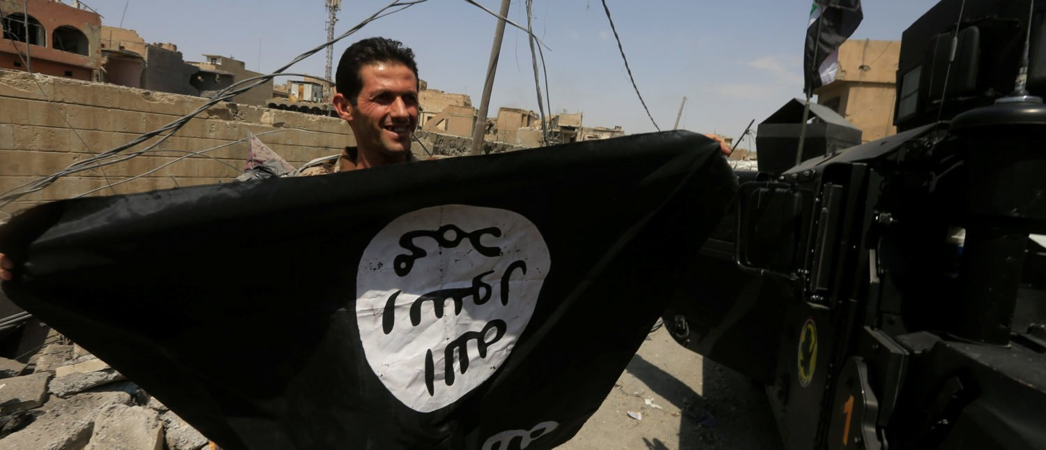 A member of Iraqi Counter Terrorism Service (CTS) holds an Islamic State militants as he celebrates in the Old City of Mosul, Iraq July 9, 2017. REUTERS/Alaa Al-Marjani - RTX3AQJH