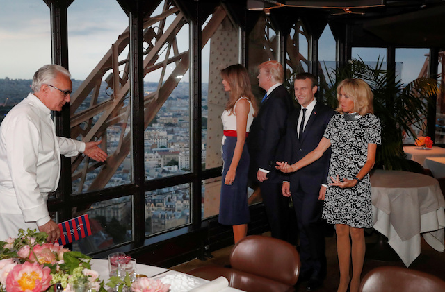 French chef Alain Ducasse (L) gestures as, from R, Brigitte Macron, wife of French President Emmanuel Macron, U.S. President Donald Trump and First lady Melania Trump gather at the Jules Verne restaurant before a private dinner at the Eiffel Tower in Paris, France, July 13, 2107. REUTERS/Yves Herman - RTX3BD3G