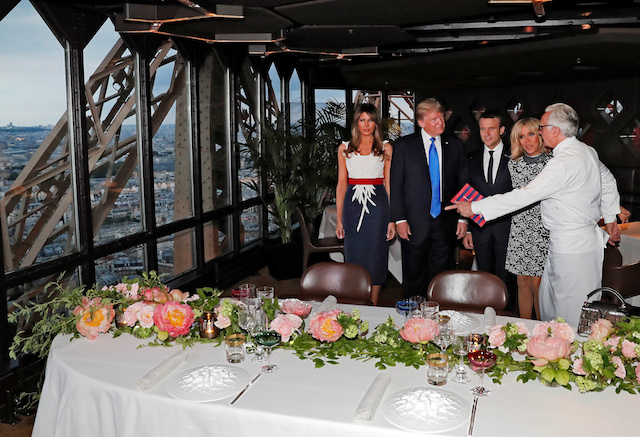 French chef Alain Ducasse (R) gestures as, from 2ndR, Brigitte Macron, wife of French President Emmanuel Macron, U.S. President Donald Trump and First lady Melania Trump gather at the Jules Verne restaurant before a private dinner at the Eiffel Tower in Paris, France, July 13, 2107. REUTERS/Yves Herman - RTX3BD4B