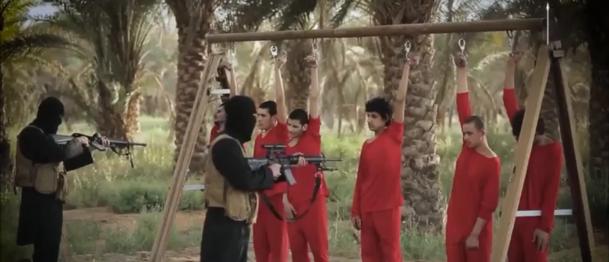 Islamic State fighters prepare to execute prisoners chained to a swing set. Source: Islamic State video screen shot