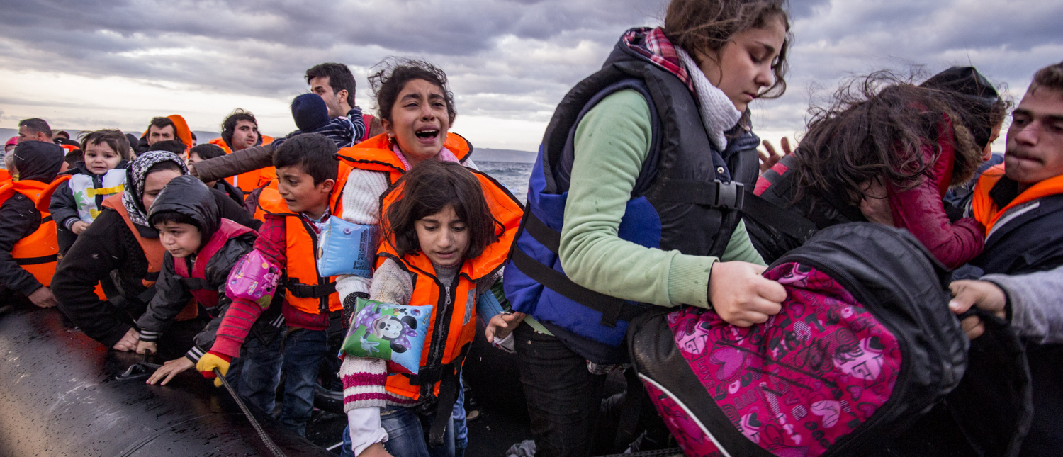 Shutterstock/ Lesvos island, Greece - 29 October 2015. Syrian migrants / refugees arrive from Turkey on boat through sea with cold water near Molyvos, Lesbos on an overload dinghy. Leaving Syria that has war. Shutterstock