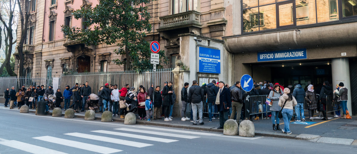 Shutterstock/ Milan, Italy - February 16, 2017: A queue for the Immigration Office in Milan, Italy. Italy is facing a refugee crisis due to ongoing wars in North Africa and the Middle East
