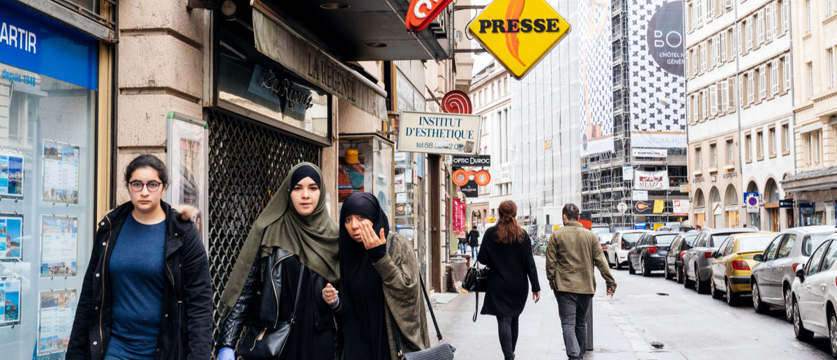 Shutterstock/ STRASBOURG, FRANCE - MAY 7, 2017: Three muslims girls walking on trottoir under Loto and press signage in French city of Strasbourg  adultarabarabianarabicasianattractivebeardbusinesscityclothesclothingculturedresseastern cultureethnicethnicityfemalefrancefriendsfriendshipfull lengthgirlhandsomeheadscarfhijabislamislamicmiddlemiddle-east culturemuslimmuslim girlsoutdoorspedestrianspeoplepersonportraitreligionscarfstrasbourgstreettourismtraditionalwalkwhitewomenyoung muslimShow more