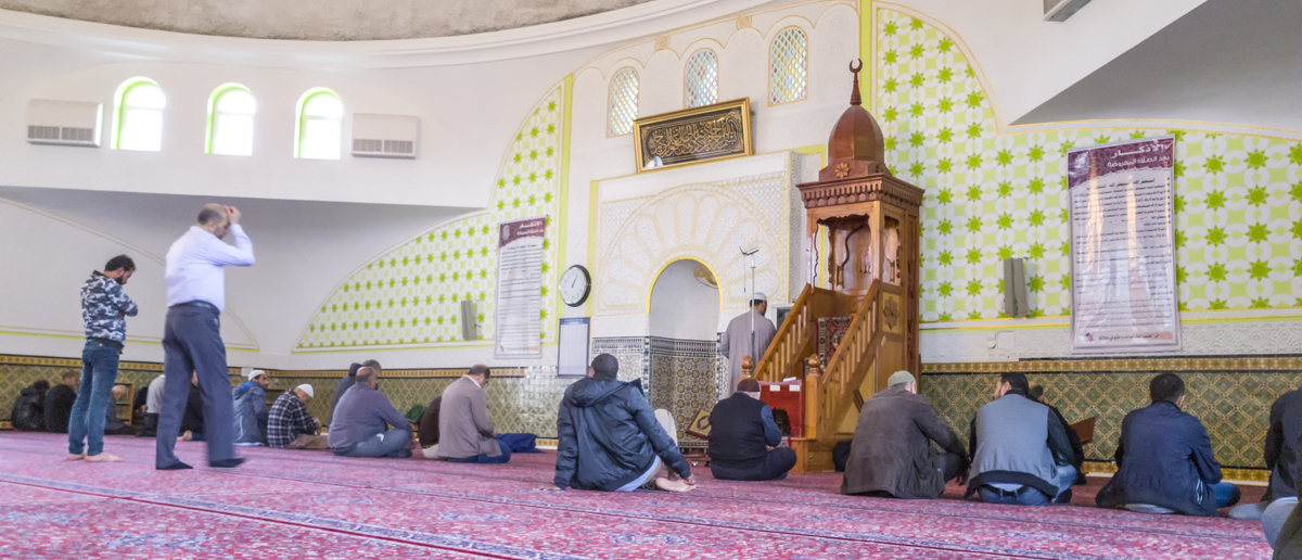 Shutterstock/ VIENA, AUSTRIA - MAY 13, 2017: Pilgrims waiting for praying inside Islamic Center of Austria.