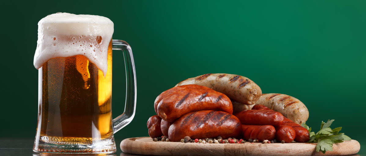 Shutterstock/ Traditional Oktoberfest menu. Beer being poured into a glass with foam, traditional snacks, sausages grilled. Copyspace with green background