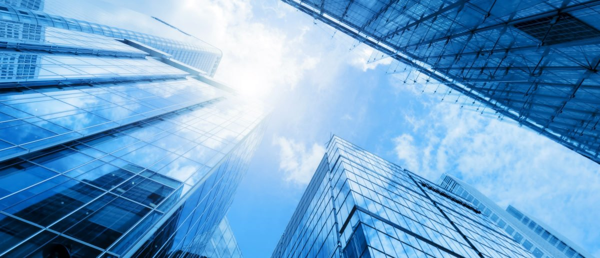 Shutterstock/ Common modern business skyscrapers, high-rise buildings, architecture raising to the sky, sun. Concepts of financial, economics, future etc. Shutterstock/ PHOTOCREO Michal Bednarek