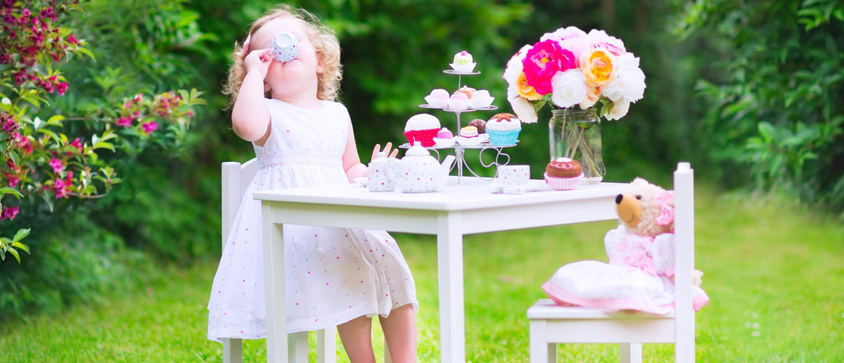 An adorable toddler girl with curly hair is playing tea party with a teddy bear. (Photo: Shutterstock
